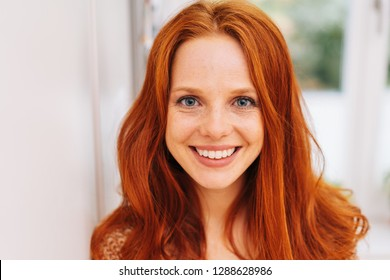 Young and pretty red-haired woman close-up front portrait, with beautiful smile, shot indoors