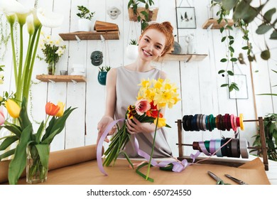 Young pretty redhead woman in dress looking camera while collecting bouquet of flowers in workshop