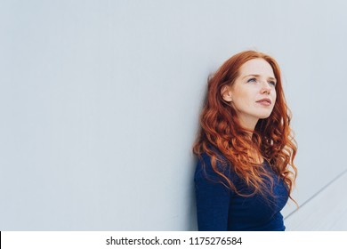 Young pretty redhead woman standing thinking deeply leaning against a white exterior wall looking up with a faraway expression