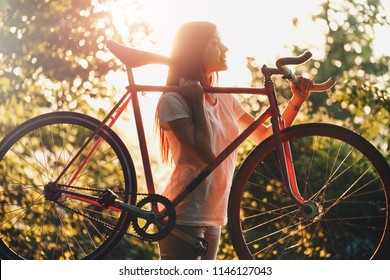 Young pretty romantic girl holding bicycle on the sunset in green summer park