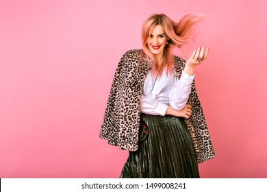 Young pretty sexy magnificent woman playing with her hairs, wearing evening sparkling cocktail outfit and fur leopard printed trendy coat, pink background, positive emotions.