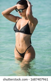 Young pretty sexy sporty woman body in black bikini in blue sea