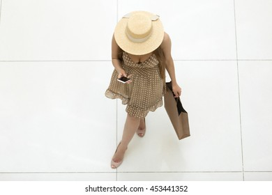 Young pretty shopper woman wearing hat and polka dot dress standing in shopping centre carrying shopping bag and holding smartphone, touching screen, reading message. View from above