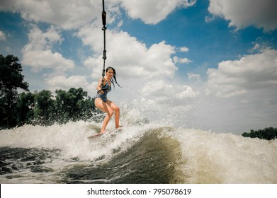 The young pretty slim brunette ladys wakeboard is towed behind a motorboat by steel wire rope