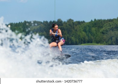 Young pretty slim brunette woman riding wakeboard on wave of motorboat in a summer lake