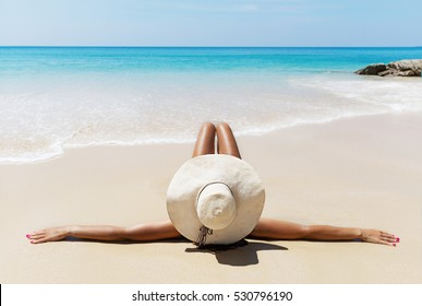 Young pretty slim brunette woman in hat and sunglasses sunbathe on the tropical beach in bikini
