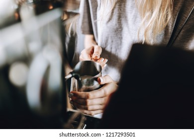 A young pretty slim girl,wearing casual outfit,is cooking coffee in a modern coffee shop. It focuses on the process.