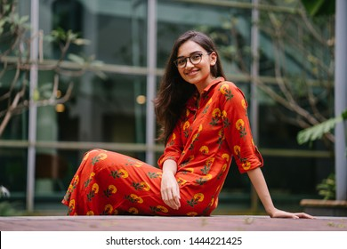 A young, pretty and slim Indian Asian woman in an ethnic orange dress and spectacles relaxes in the sun on a street in the city on her own.