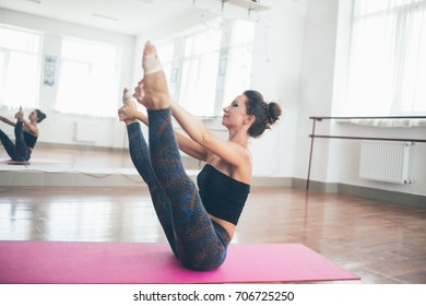 Young pretty slim woman is doing yoga to stretch her legs