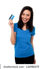 Young pretty smiling asian girl showing her credit card to the camera.