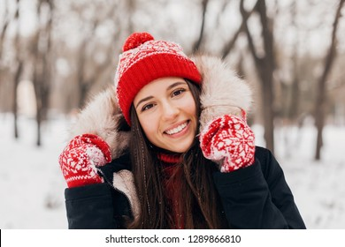 young pretty smiling happy woman in red mittens and knitted hat wearing winter coat with fur hood, walking in park in snow, warm clothes