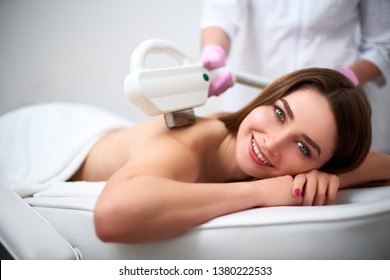 Young pretty smiling woman back laser epilation in beauty salon. Cosmetologist doing depilation treatment with elos device. Beautician hands in gloves holding hair removal cosmetology ipl hardware