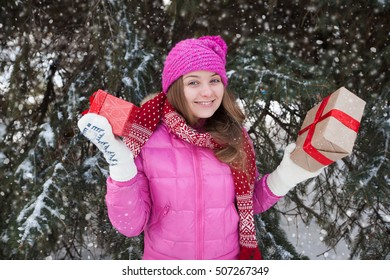 the young pretty smiling woman with a Christmas gift outdoors. x-mas, winter, happiness concept.