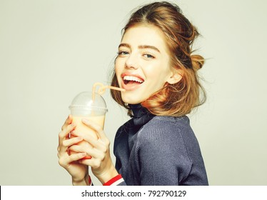 young pretty smiling woman or cute sexy girl with long hair drinking fresh juice or fruit yoghurt from bottle or glass with orange straw, poses on grey background
