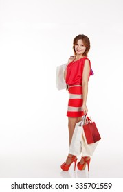 young pretty smiling woman in red dress and shoes standing with shopping bags