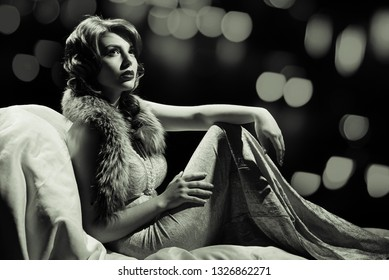 Young pretty smiling woman in retro clothing lying in armchair, black and white photography in retro style