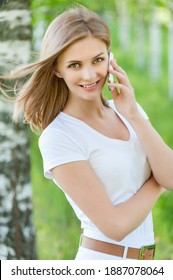 Young pretty smiling woman in a white blouse talking on a mobile phone against the background of a summer green city park.