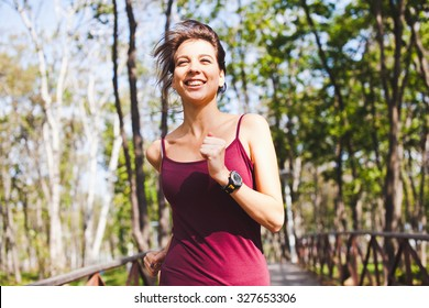 Young pretty sporty smiling woman running in forest wearing sport gadget pulse meter running tracker on wrist. Front view with central position