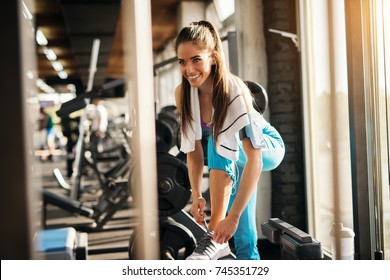 Young pretty sporty woman tying shoelaces in the gym while listening music.