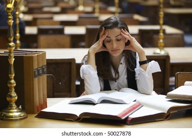 Young pretty student sitting at desk in old university library studying books.