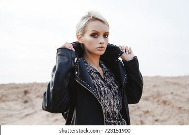 Young pretty stylish girl in black leather jacket posing, walking outdoors. Fashionable blonde woman with short hair looking at you
