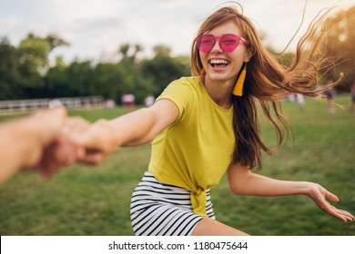 young pretty stylish smiling woman having fun in city park, holding hand of boyfriend, follow me, positive, emotional, wearing yellow top, pink sunglasses, summer style fashion trend, positive emotion