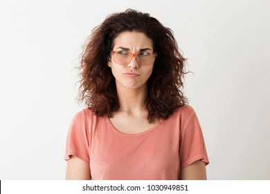 young pretty stylish woman in glasses thinking, pensive face expression, curly hair, having problem, funny emotion, isolated on white background, pink t-shirt, hipster style, student, frowning