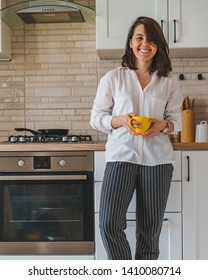young pretty stylish woman holding yellow mug at white kitchen. housewife concept