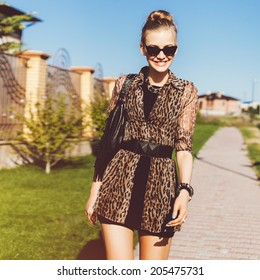 Young pretty stylish woman walking alone at beautiful summer day in short black dress and leopard printed shirt, wearing cat eye sunglasses, smiling an having fun.