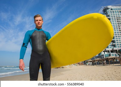Young pretty surfer with wet suit boy holding yellow surfboard on the beach up front.