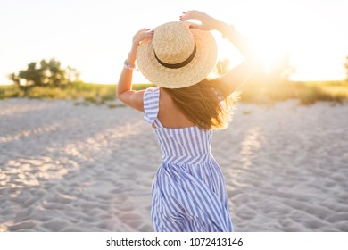 Young pretty  tanned woman standing on the beach near the sea back waiting and dreaming about. Wearing straw hat and striped dress. Amazing sunset light.