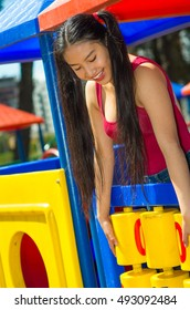 Young pretty teenage girl with pig tails wearing purple top, standing inside plahouse tower smiling happily, playground concept