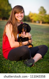 Young pretty teenage girl sitting in the grass with a puppy
