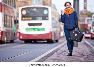 Young pretty teenage girl walking in the middle of Princess street in Edinburgh city
