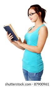 Young pretty teenage student standing and reading a book. Isolated on white.