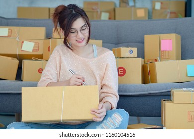Young pretty teenage work at home writing parcel box in her hands. New generation life style of young entrepreneur