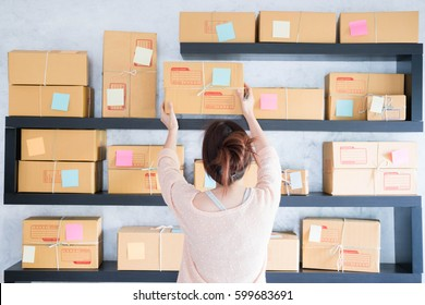 Young pretty teenage work at home write note on parcel box. New generation life style of young entrepreneur