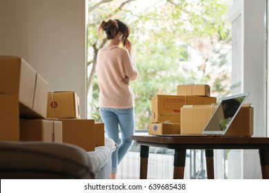 Young pretty teenage work at home with laptop prepare product in parcel for customer. New generation life style of young entrepreneur