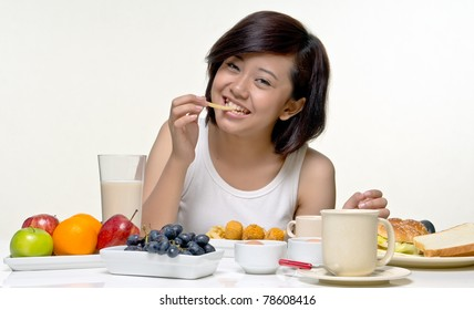 Young pretty teenager smiles while eating fries for morning breakfast, isolated background