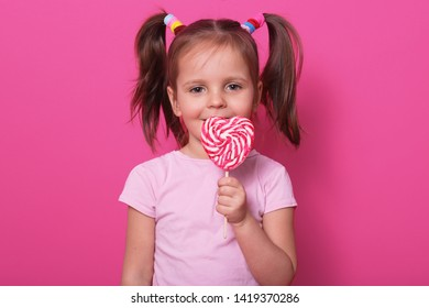Young pretty toddler girl kid with big sweet lollypop candy in rose casual t shirt posing isolated over pink studio background, has two funny ponitails with colourful scrinchies. Childhood concept.