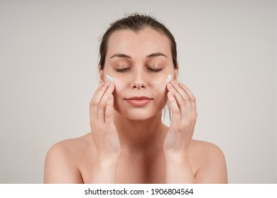 young pretty topless woman applying nourishing cream to face, eyes closed, isolate on gray background.