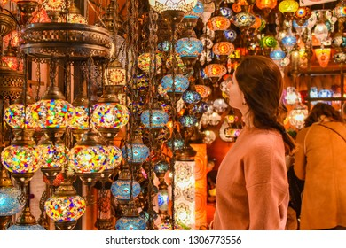 Young pretty tourist woman looking on Traditional Turkish lamps in souvenir shop. Shopping in the Grand Bazar. Shopping tour in Istanbul, Turkey.