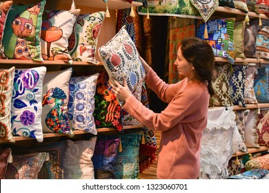 Young pretty tourist woman looking on Traditional Turkish pillows in souvenir shop. Shopping in the Grand Bazar. Shopping tour in Istanbul, Turkey.