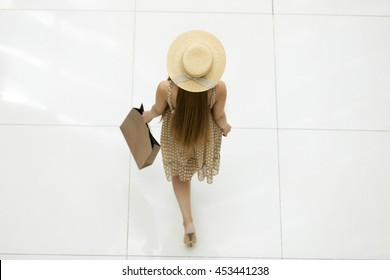 Young pretty traveler woman walking in the shopping centre carrying shopping bag wearing dress and a hat. View from above, rear view