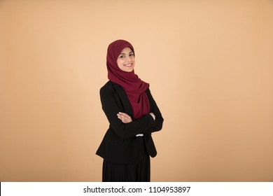 Young pretty veiled girl standing crossed arms in a side shot on a beige background.