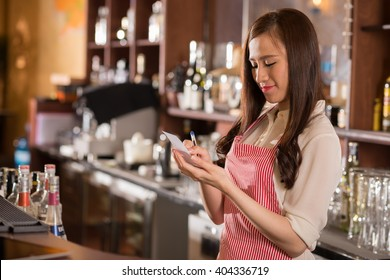 Young pretty waitress reading order in her notepad