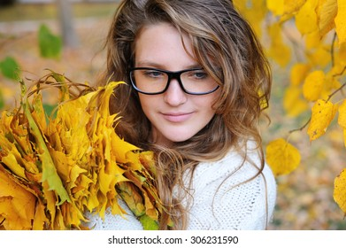 Young pretty woman in the autumn park makes a wreath of leaves