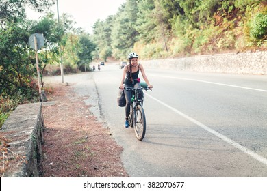 Young pretty woman with backpack and helmet travels with bicycle outdoors on the asphalt road