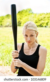 Young pretty woman with baseball bat, against green of summer park.