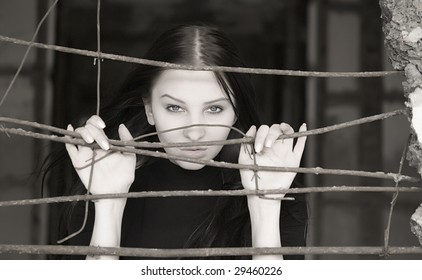 young pretty woman behind iron grid